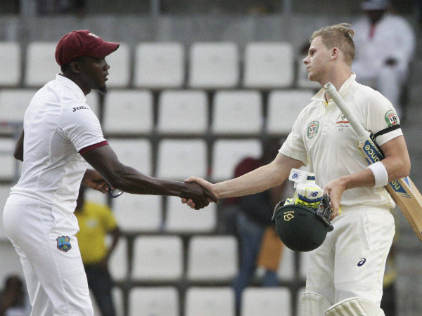 Jerome Taylor, left, shakes hands with Steve Smith at the end of their first Test