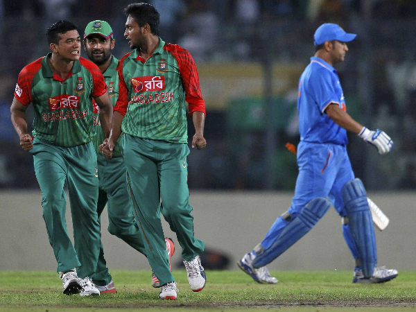 Dhoni (right) walks back to the pavilion after being dismissed by Shakib (second right)
