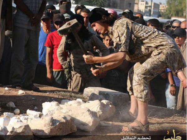An ISIS militant destroys artifacts with sledgehammers