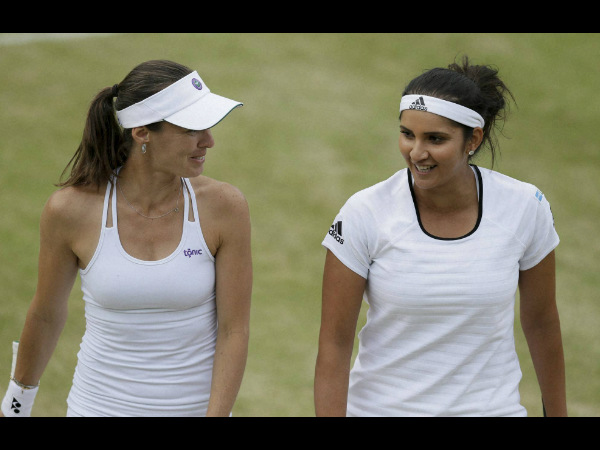 Martina Hingis, left, and Sania Mirza, talk between points during their doubles match against Casey Dellacqua and Yaroslava Shvedova