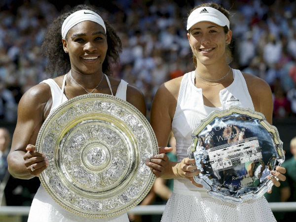 Serena Williams, left and Garbine Muguruza hold up their trophies