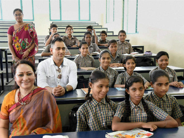 Dhoni along with the students in a classroom during a programme at a school in Bokaro, Jharkhand on Tuesday.