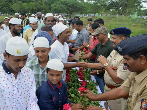 Police personnel offer roses to Muslims on Eid