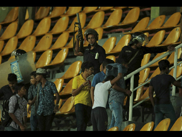 Sri Lankan riot police officers lead spectators out of the stands following a clash