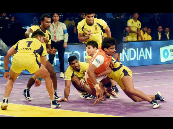 Players in action during a Pro Kabaddi League match between Telugu Titans (yellow) and Puneri Paltan (orange) in Mumbai on Monday.