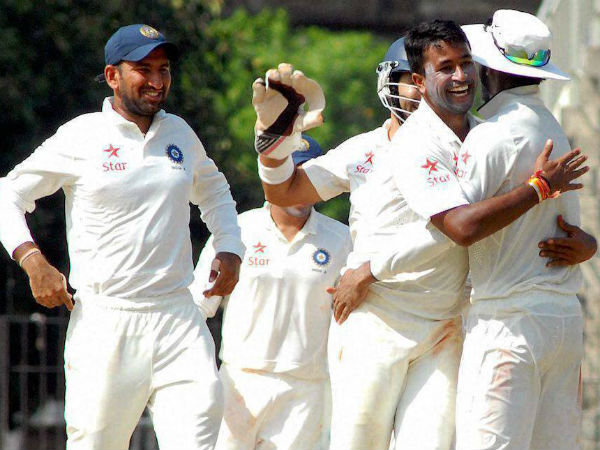 Ojha (second right) celebrates with team-mates after taking a wicket