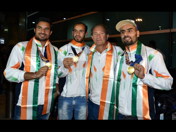File photo: Gurbaj Singh (left), Indian hockey team's high performance director Roelant Oltman (2nd right), Ramandeep Singh and Gurwinder Singh Chandi (right) pose with their Asian Games gold medals upon arrival at IGI airport New Delhi on October 5, 2014