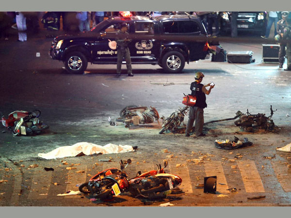 A policeman photographs debris from an explosion in central Bangkok, Thailand, Monday, Aug. 17, 2015. A large explosion rocked a central Bangkok intersection during the evening rush hour, killing at least three people and injuring 25 others, police said.