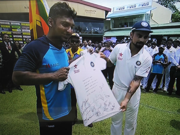 Kohli (right) presents his jersey (signed by Indian players) to Sangakkara