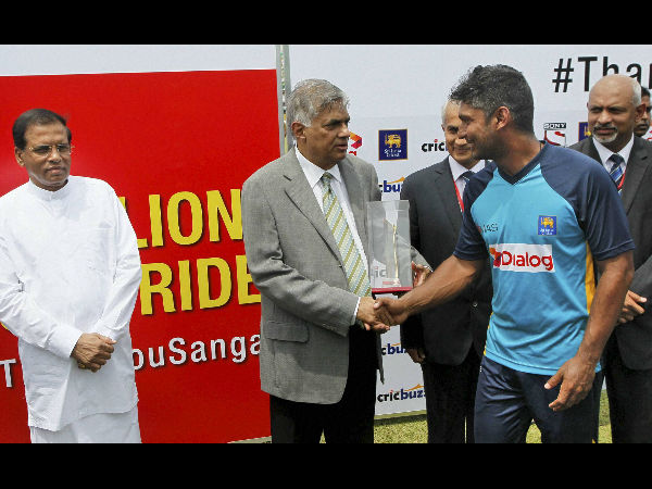 Sri Lankan Prime Minister Ranil Wickremesinghe hands over a moment to Kumar Sangakkara as President Maithripala Sirisena, left, looks on at the end of the second Test