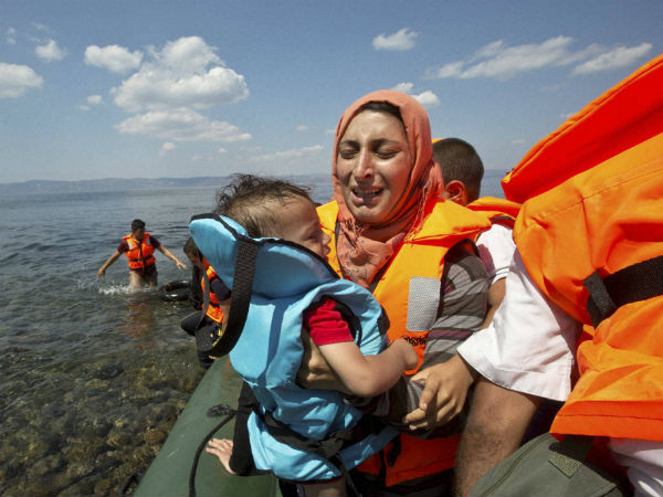 Syrian migrant mother holding her child breaks into tears