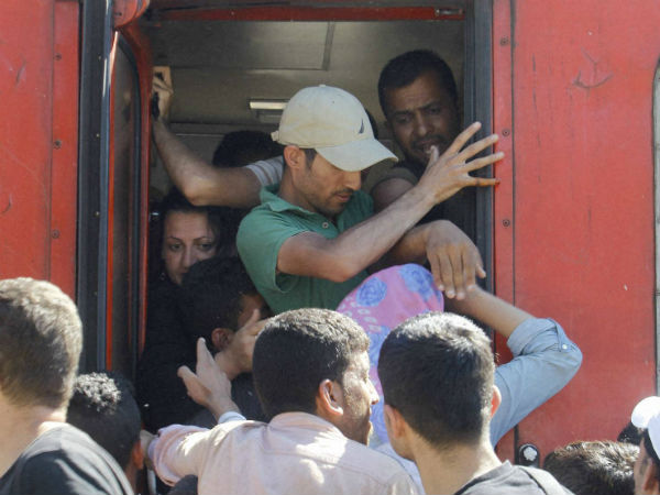 Migrants push each other trying to secure a place in train