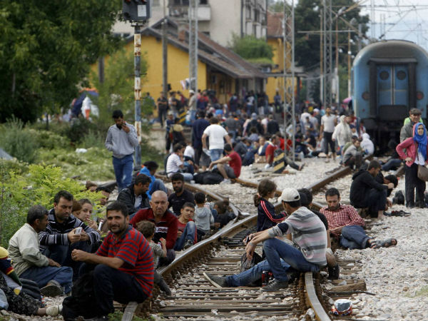 Migrants sit on the tracks at the railway station