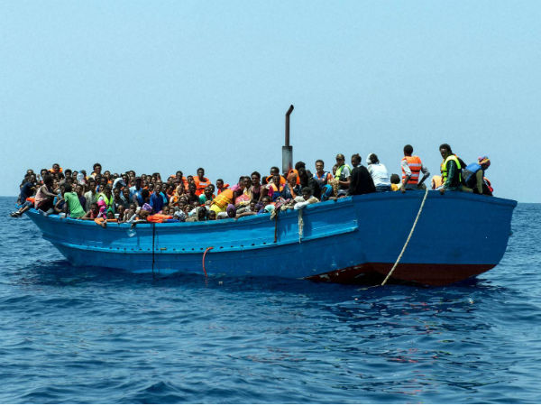 Migrants stand on a wooden boat in the Mediterranean Sea