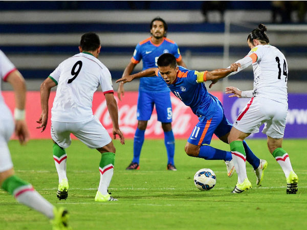 India's captain Sunil Chettri (Blue) vies for possession of the ball with Andranik Teymourian of Iran