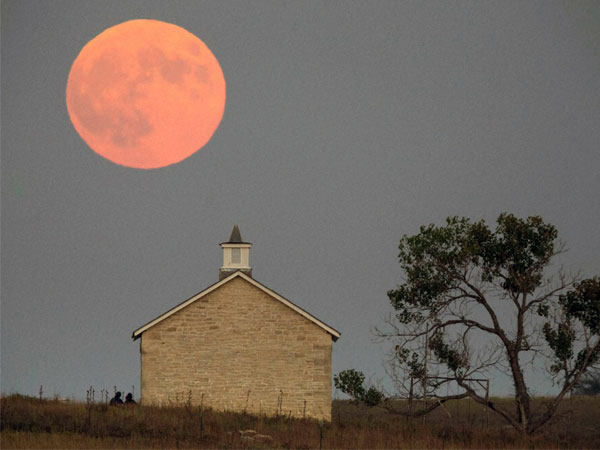 Strong City : A super moon rises over the Lower Fox Creek School near Strong City, Kan., Sunday, Sept. 27, 2015. It was the first time Sunday since 1982 that a total lunar eclipse was combined with a supermoon.