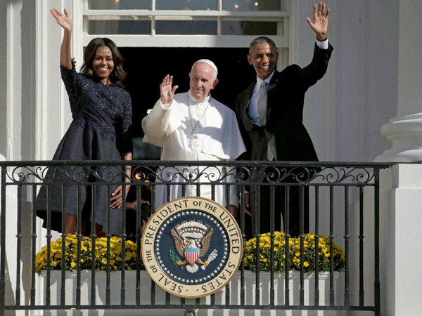 President Barack Obama, first lady Michelle Obama and Pope Francis wave to the crowd on the South Lawn from the Truman Balcony of the White House in Washington