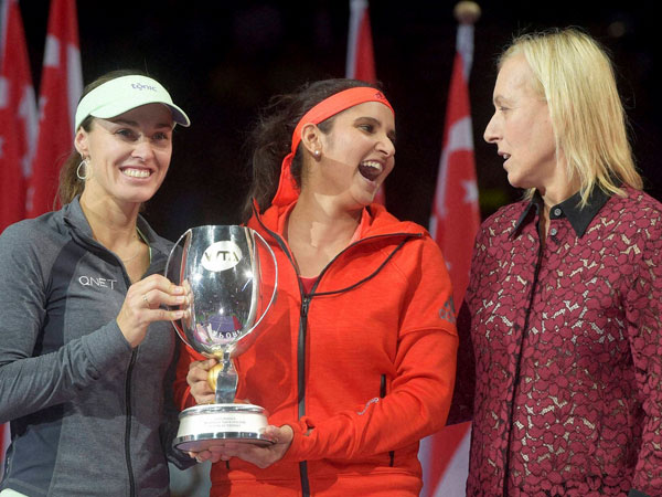 Sania Mirza of India, center, laughs and speaks to retired tennis player Martina Navratilova as she and her partner, Martina Hingis of Switzerland, left, are presented with their trophy after winning the doubles event at the WTA tennis finals in Singapore.