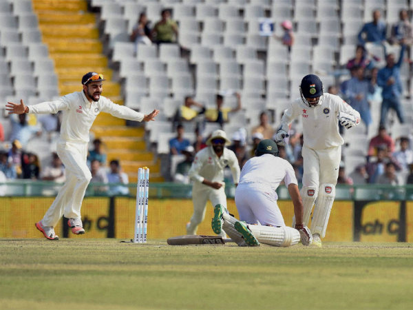 Kohli (left) is ecstatic after Amla (on the ground) is stumped by Saha (right) off Ashwin (not in picture)