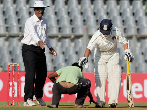 File photo: A fan runs on to the field to touch 'God' Tendulkar's feet during a Ranji Trophy game