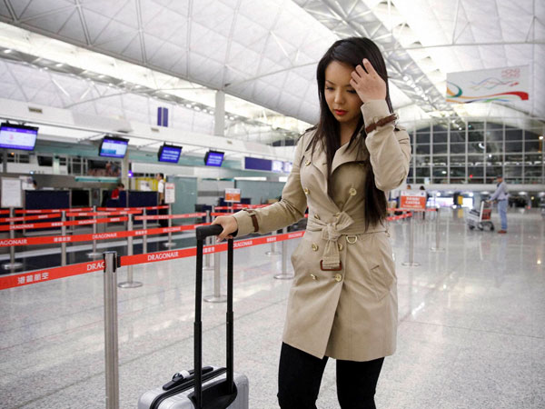 Canada's Miss World contestant Anastasia Lin walks away from the airline counter after she was denied entry to mainland China, at Hong Kong International Airport in Hong Kong.