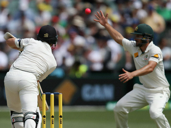 Kane Williamson (left) plays a shot as Joe Burns attempts to field on day 1 of day-night Test