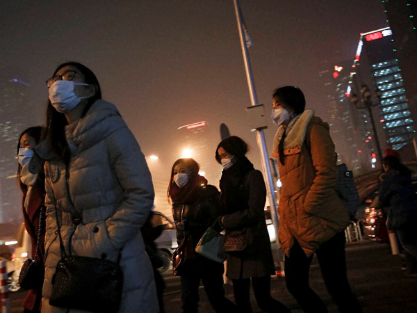 Women wearing masks to protect themselves from pollutants walk to a subway station on a polluted day in Beijing, Tuesday, Dec. 8, 2015. Beijing's red alerts for smog are as much about duration as they are about severity of pollution forecasts. The forecasting model must predict three or more days of smog with levels of 300 or higher on the city's air quality index - which typically would include having levels of dangerous PM 2.5 particles of about 10 times the safe level.