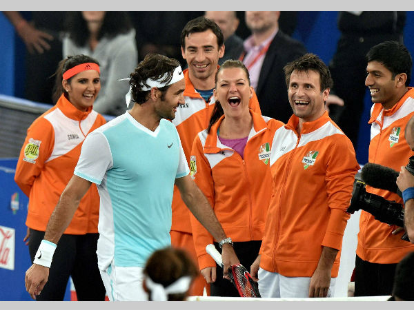 UAE Royals' Roger Federer walks past Indian Aces players during IPTL in Delhi