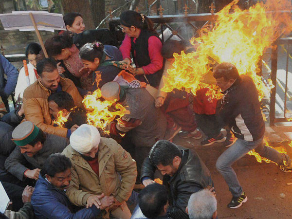Activists of Congress party try to flee after their clothes caught fire while they were trying to burn an effigy of Prime Minister Narendra Modi during a protest in Shimla on Monday.