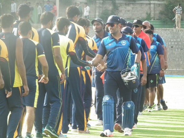 MS Dhoni (right) shakes hands with Karnataka players after the match. Photo by Aprameya .C