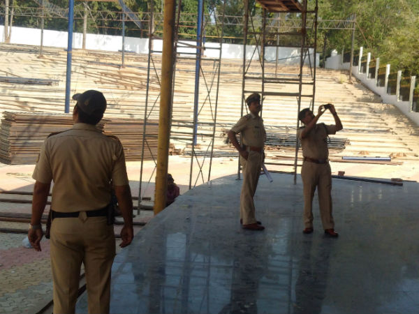 Police officials inspect the amphitheater under renovation for PM's address.