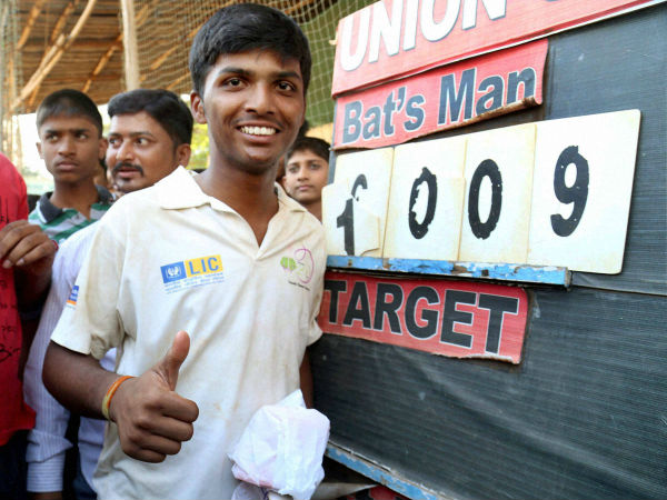 Pranav poses in front of the scoreboard which reads 1009