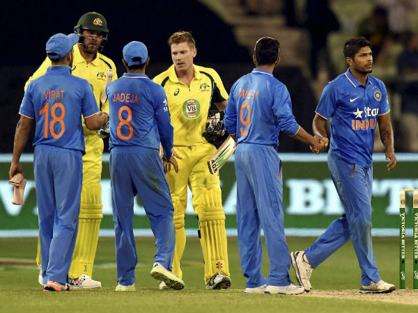 John Hastings, 2nd left, and James Faulkner, centre right, shake hands with Indian players after defeating them in the 3rd ODI at MCG