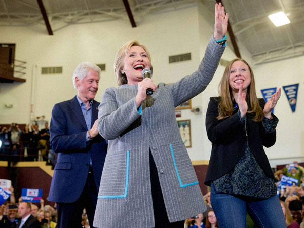 Democratic presidential candidate Hillary Clinton, accompanied by her husband, former President Bill Clinton and their daughter Chelsea Clinton, waves as she arrives to speak at a rally at Abraham Lincoln High School in Des Moines, Iowa.