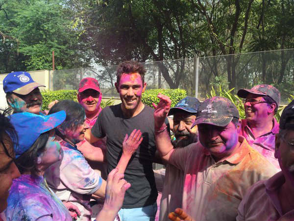 Glenn Maxwell (centre, in black T-shirt) plays Holi. Photo from Cricket Australia's (CA) Twitter page