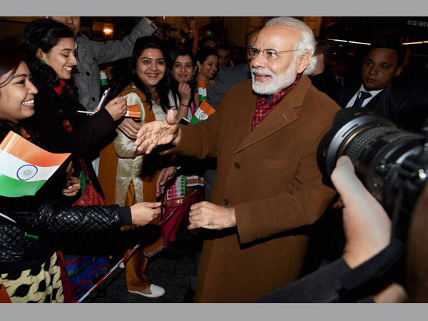 Prime Minister Narendra Modi meets Indian community people outside his hotel on his arrival in Brussels on Wednesday.