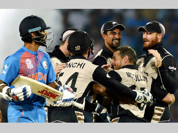 New Zealand players (right) celebrate the dismissal of Shikhar Dhawan (left)