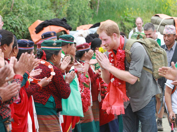 In this handout photo provided by National News Agency of Nepal, Britain's Prince Harry is welcomed by the villagers upon his arrival in Lamjung, Nepal, Monday, March 21