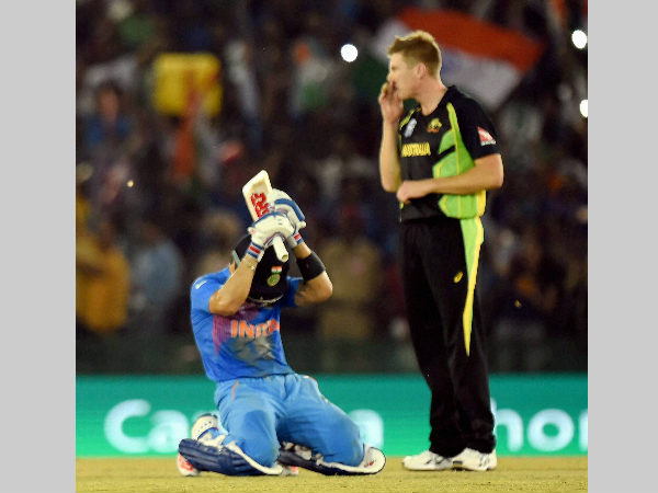 An emotional Kohli (left) is down on his knees after securing India's victory. Australia's James Faulkner watches on