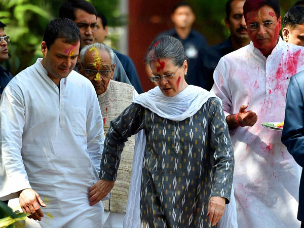 Congress President Sonia Gandhi and her son and party's Vice President Rahul Gandhi arrive to celebrate Holi with party workers at All India Congress Committee headquarters (AICC) in New Delhi on Thursday.