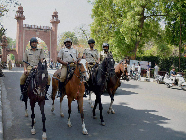 Police force deployed infront of Aligarh Muslim University gate after the clashes between two groups at University campus, in Aligarh on Sunday.