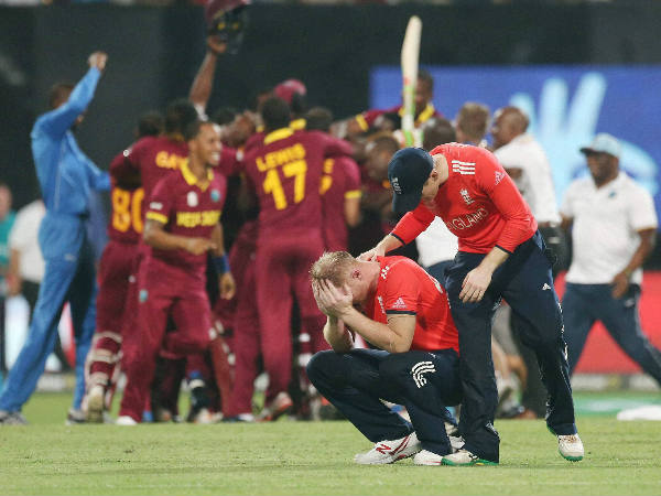 Foreground: Ben Stokes (left) is consoled by Eoin Morgan after the match as West Indies players celebrate in the background