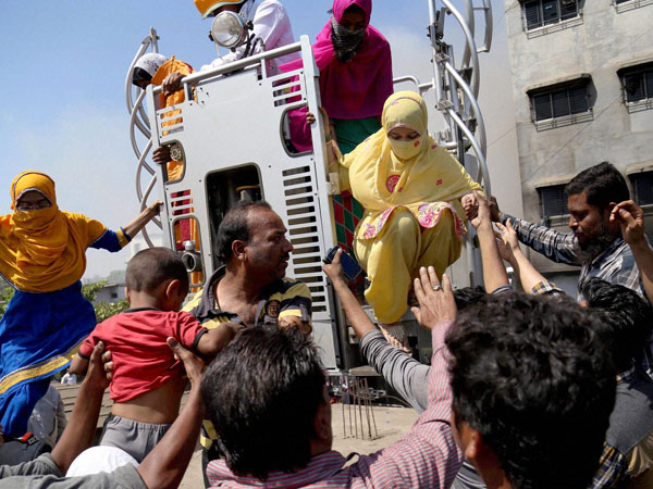 Fire brigade team rescue people after a fire broke out in a factory at Bhiwandi in Mumbai on Tuesday.
