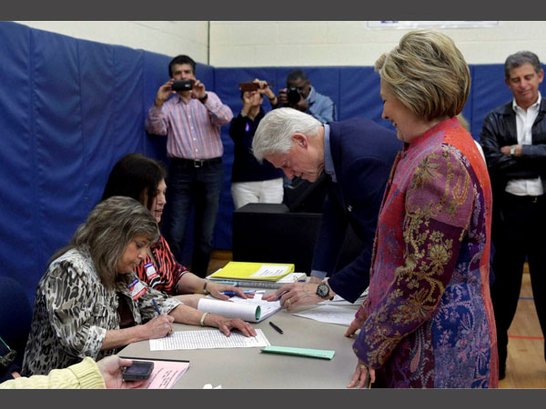 Democratic presidential candidate Hillary Clinton and her husband, former President Bill Clinton, sign in at their voting place at the Grafflin Elementary School in Chappaqua, N.Y., Tuesday, April 19, 2016.