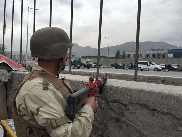 An Afghan soldier responds to a Taliban-claimed suicide attack in Kabul, Afghanistan.