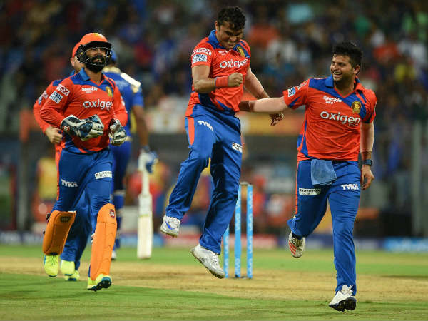 Gujarat's Pravin Tambe (centre) celebrates with captain Suresh Raina (right) after dismissing Kieron Pollard