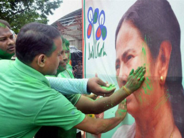 TMC supporters smear color on a poster of Mamata Banerjee in Agartala