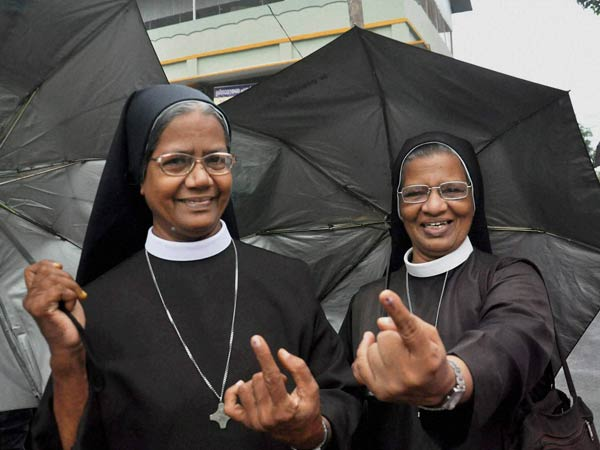 Catholic nuns show their fingers after casting votes outside a polling booth during the assembly elections in Kochi, Kerala on Monday.