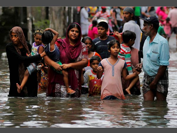 Sri Lankans wade through a road submerged in flood waters in Colombo, Sri Lanka, Tuesday, May 17, 2016. The Disaster Management Center said that 114 homes have been destroyed and more than 137,000 people have been evacuated to safe locations as heavy rains continue.