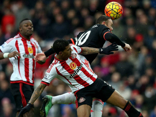 Sunderland's Patrick Van Aanholt, front, vies for the ball with Manchester United's captain Wayne Rooney during English Premier League.